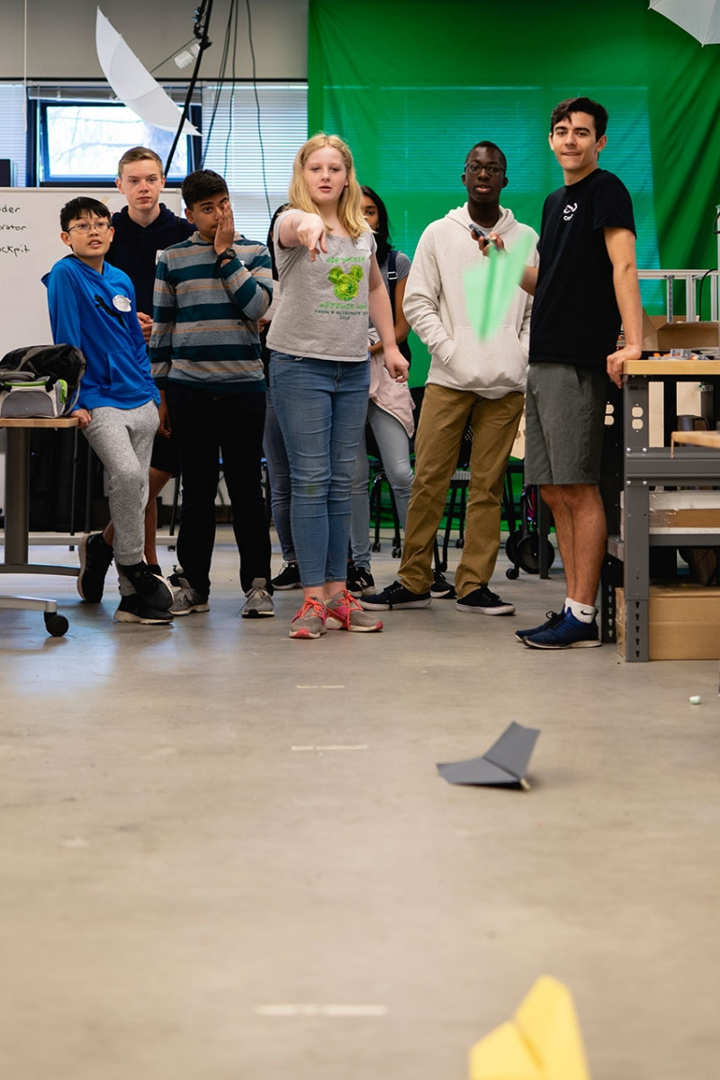A student throws paper airplanes while a group of students look on