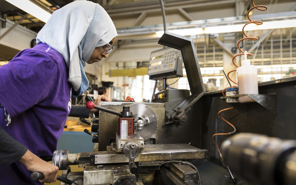 Fethya Ibrahim operating a machine