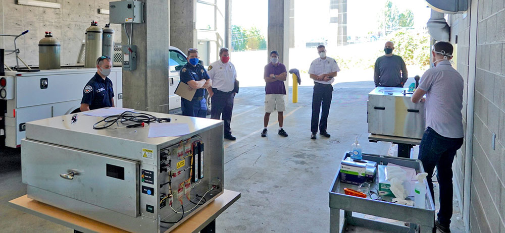 A training involving 6 people in masks standing in a distanced circle in a loading dock while UW PhD student Ben Sullivan gestures to a UVC decontamination box.
