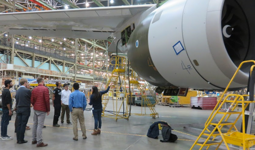 Students standing under wing of a jet in a Boeing plant