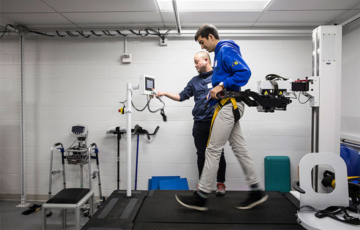 A student walking on treadmill with devices hooked up to him