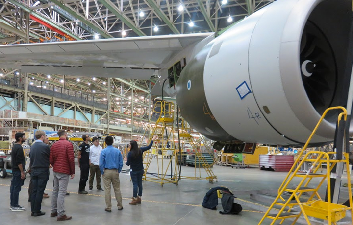 students standing below jet wing in Boeing plant