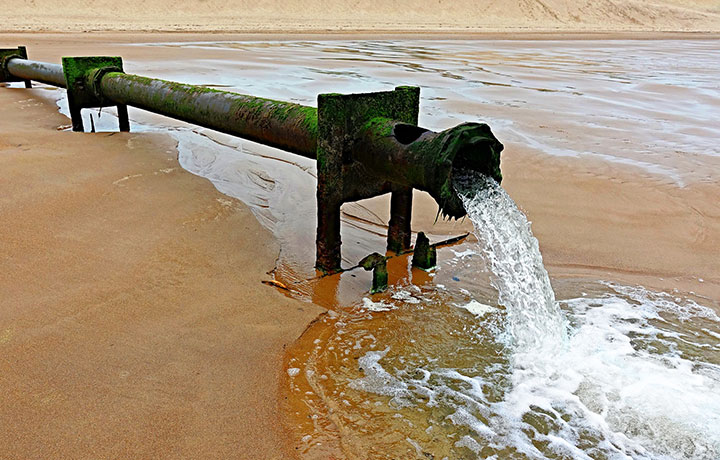 Water gushing out of a pipe on a beach