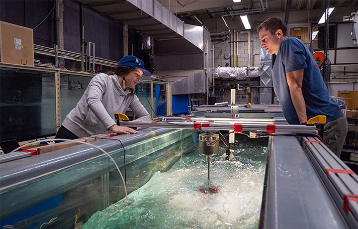 Abigale Snortland and Greg Talpey observe a cross-flow turbine in the Alice C. Tyler flume in the UW Harris Hydraulics Lab