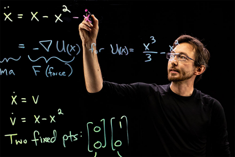 Professor Steve Brunton writing math equations on a lightboard with a marker