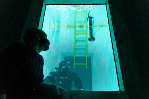 Trevor Harrison looking through the glass pane of a big water tank with a diver and a µFloat inside