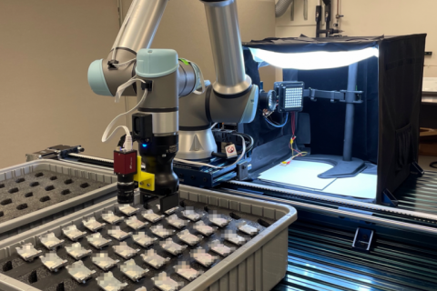 A robot arm is positioned over a case full of a set of identical metal parts arranged in a 7x5 array.