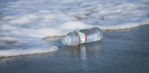 A plastic water bottle sits in the ocean surf