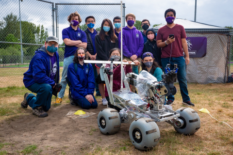 A team of 12 people in covid masks stand outdoors in a group behind a robot that looks like a mars rover