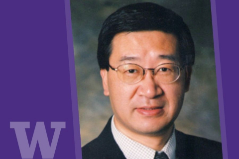 professional-style headshot photo of man in glasses and suit with UW logo in lower left