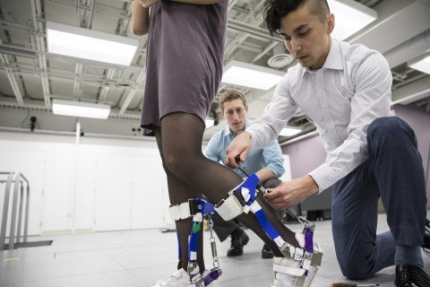 A researcher adjusting device on another person's legs