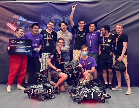 Ten students, several wearing purple, stand in a group with two small wheeled robots in front of them