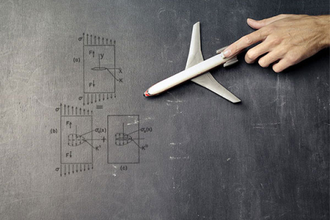 A hand pointing at a model airplane