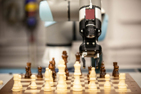 A robot arm hovering above a chessboard