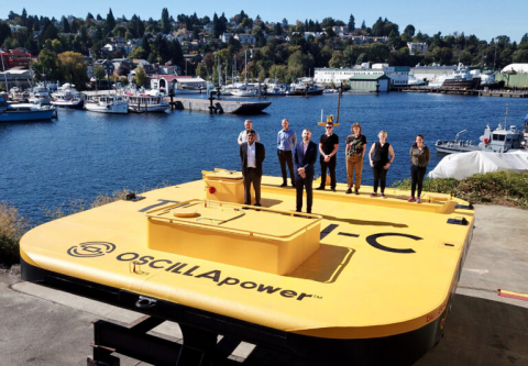 A group of 8 people stand on a large yellow wave energy converter