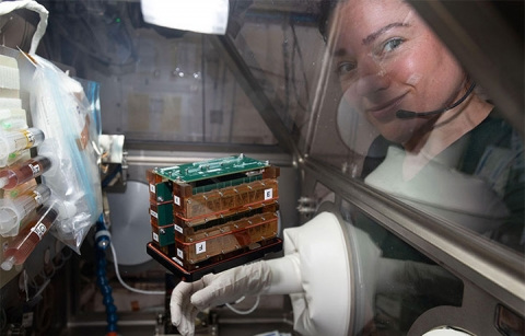 An astronaut next to a device floating in space